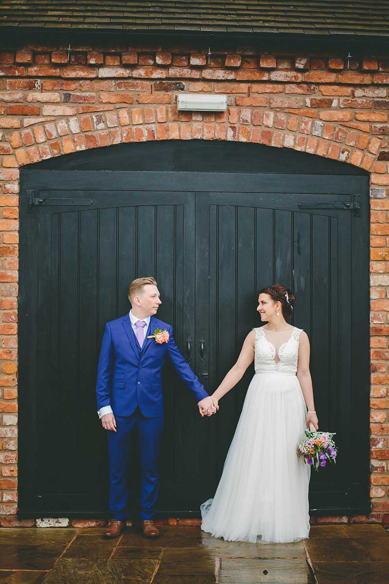 Bride and groom holding hands infront of the barn at curradine barns
