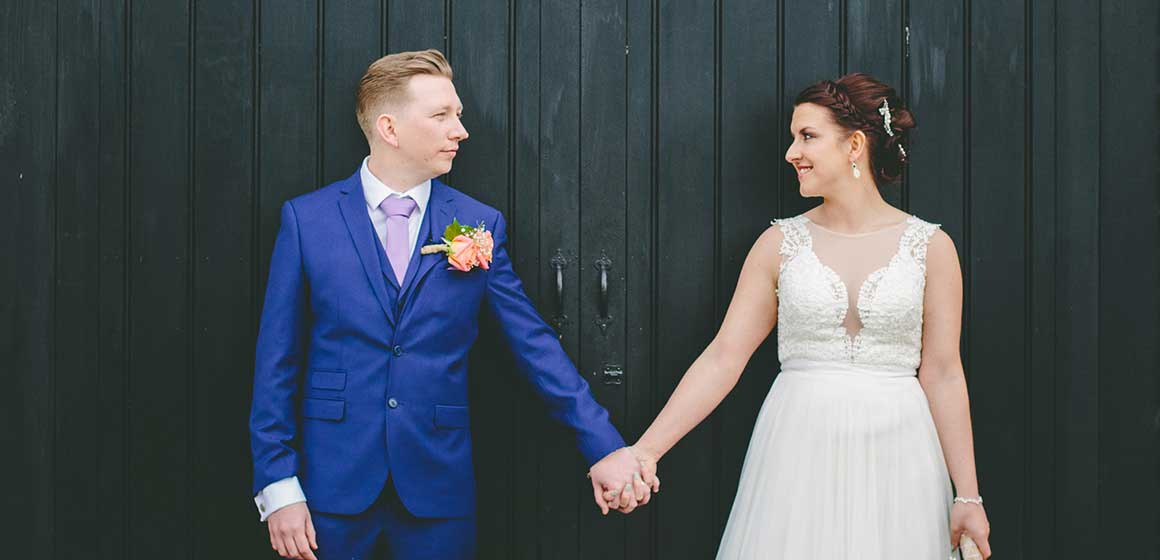 Bride and groom holding hands outside of Curradine Barns