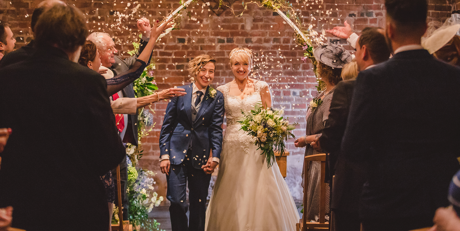 The wedding party celebrate the newlyweds with confetti at this beautiful Worcestershire wedding venue