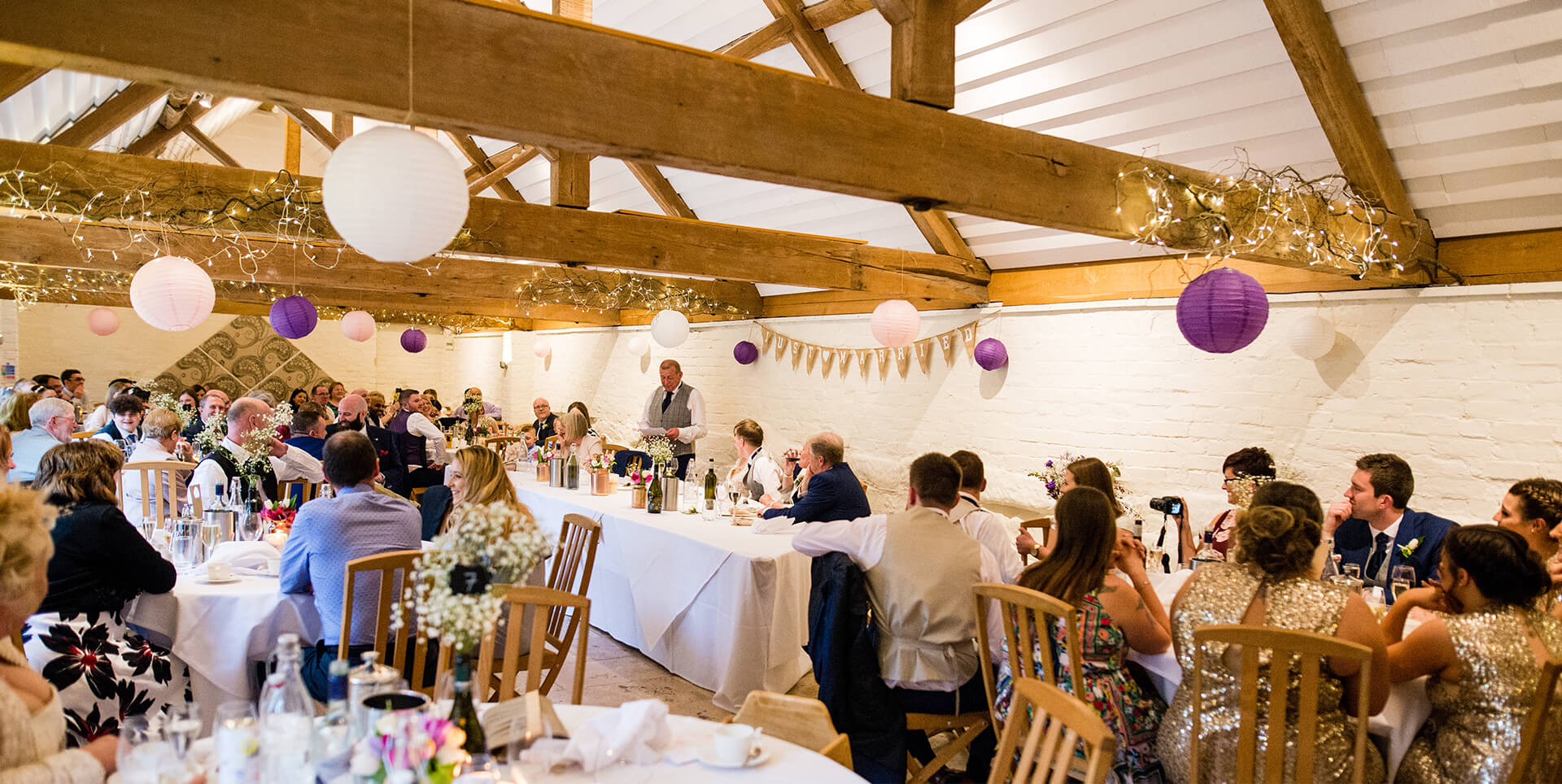 Guests sitting down to enjoy the father of the bride speech at this Worcestershire barn wedding venue