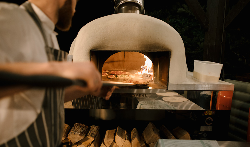 curradine barns chef cooks pizza in woodfired oven